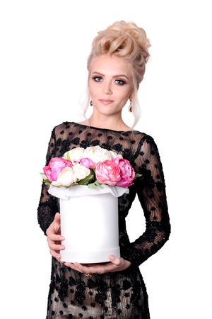 Beautiful blonde woman in elegant black evening dress with updo hairstyle holding a giftbox, bouquet of flowers in her hands. Fashion photo. Foto de archivo