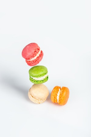 Different types of macaroons in motion falling on white background. Traditional french dessert isolated on white with space for text.