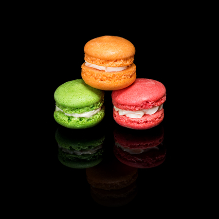 Multicolored macaroons isolated on black background with reflection. Stock Photo