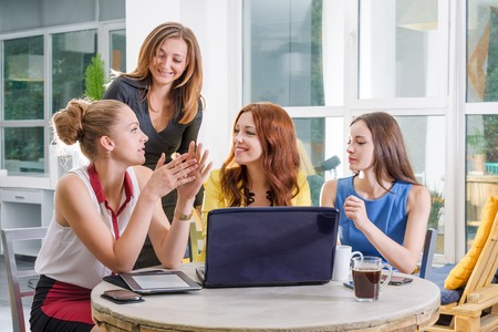 Group of four pretty businesswoman working togeather with new startup project using laptop computer in modern loft. People and teamwork concept - happy creative team in office. Women in businness.