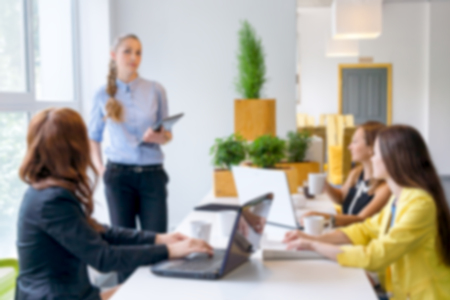 businness: Blurred background. Pretty young business woman giving a presentation in conference or meeting setting. People and teamwork concept - happy creative team in office. Women in businness. Stock Photo