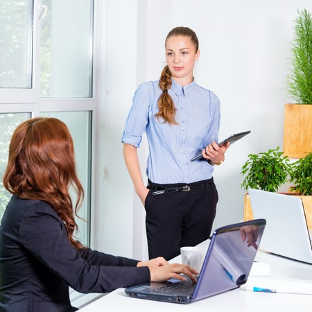 businness: Pretty young business woman giving a presentation in conference or meeting setting. People and teamwork concept - happy creative team in office. Women in businness. Stock Photo