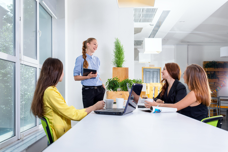 Pretty young business woman giving a presentation in conference or meeting setting. People and teamwork concept - happy creative team in office. Women in businness. Stock Photo