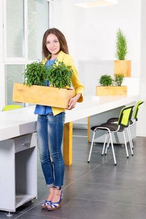 Green living. Attractive young businesswoman standing in modern loft office holding a box with plants. Environmental scientist or biologist at work. Student in biology and ecology. Eco concept.