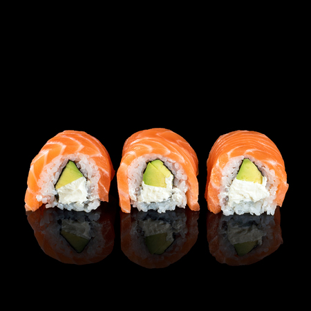 Sushi rolls made of fresh raw salmon, cream cheese and avocado isolated on black with reflections. Free space for text.