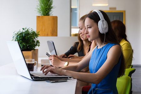 businness: Group of pretty businesswoman working together with new startup project using laptop computer in modern loft. People and teamwork concept - happy creative team in office. Women in businness.