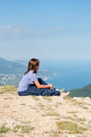mujer mirando el horizonte: Young woman relaxing on a rock and enjoying the beauty of seascape sitiing on the mountain top. Travel, Healthy Lifestyle concept