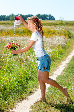 Beautiful blonde girl walking barefoot on summer field with a bouquet of wild flowers