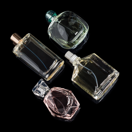 Different perfume bottles with reflections on black background. Perfumery, cosmetics.