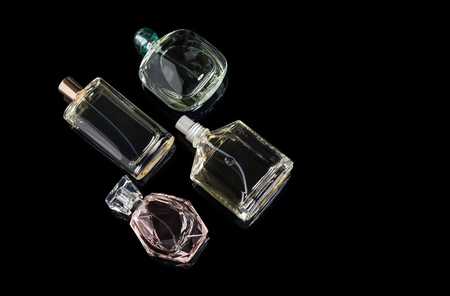 Different perfume bottles with reflections on black background with space for text. Perfumery, cosmetics.