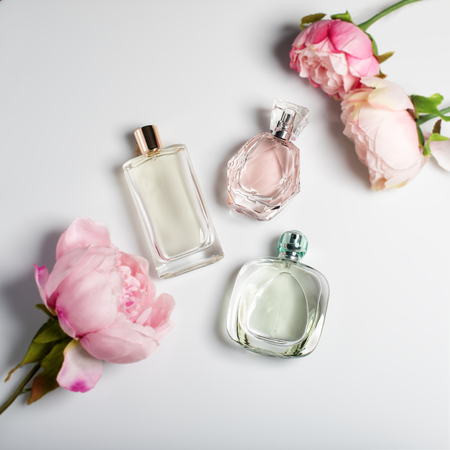 Perfume bottles with flowers on light background. Perfumery, cosmetics, fragrance collection. Flat lay Фото со стока - 73687197