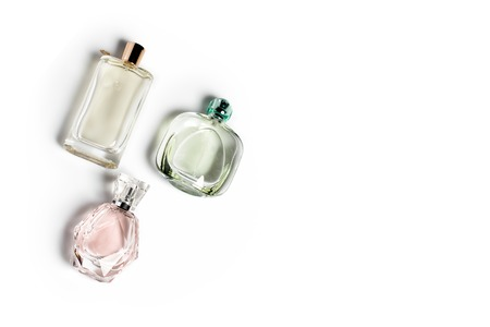 Perfume bottles on light background. Perfumery, cosmetics, fragrance collection. Free space for text.