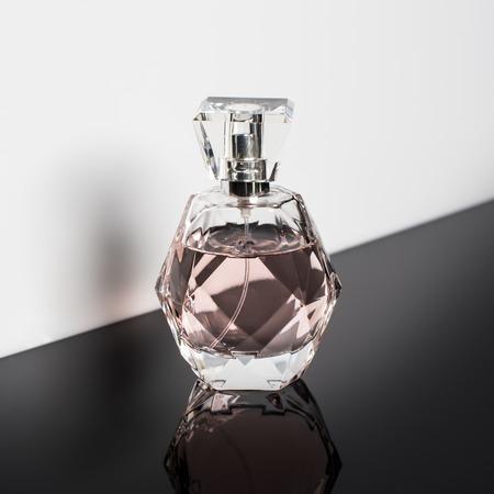 Perfume bottle with reflection on white background. Perfumery, cosmetics.