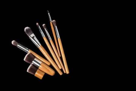 Collection of professional makeup brushes on black background with space for text