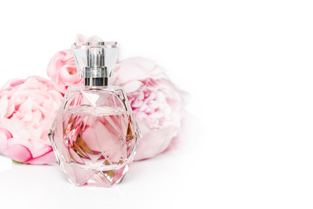 Pink perfume bottle with flowers on light background. Perfumery, cosmetics, fragrance collection