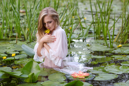 Young woman beauty portrait in water. Girl with gentle makeup in the lake among lotuses and water lilies. Outdoor fashion photo Stock Photo