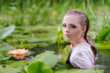 Young woman beauty portrait in water. Girl with gentle makeup in the lake among lotuses and water lilies. Outdoor fashion photo Reklamní fotografie