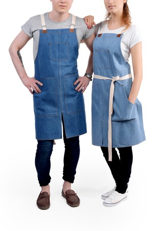 Young chefs or waiters man and woman posing, wearing aprons isolated on white background.