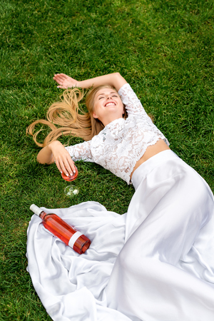 wine  pink: Beautiful woman drinking wine outdoors. Portrait of young blonde beauty in the vineyards having fun, enjoying a glass of wine in the garden or tasting alcohol cocktail in lawn. Stock Photo