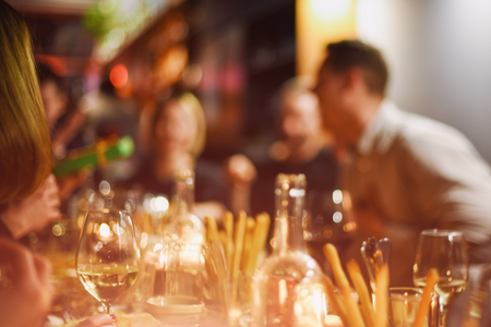 Abstract blurred group of friends meeting in the restaurant. Blurry background of caucasian people having fun, eating and celedrating together. Lifestyle, friendship, party concept Stock Photo