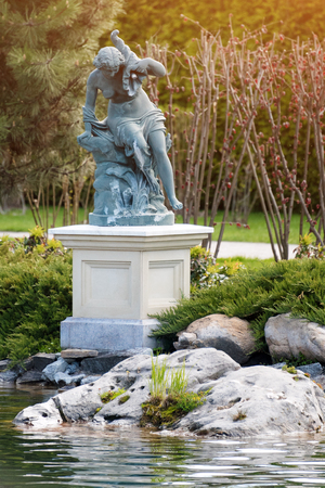 Fountain with statue of a woman in the park near the lake