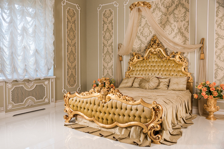 Luxury bedroom in light colors with golden furniture details. Big comfortable double royal bed in elegant classic interior 免版税图像