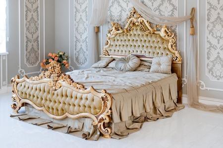 Luxury bedroom in light colors with golden furniture details. Big comfortable double royal bed in elegant classic interior Standard-Bild
