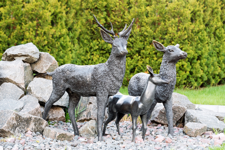 Statue of the deer in the park. Male deer protecting his family Stock Photo