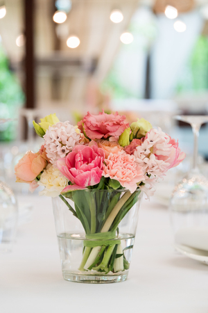 Flower table decorations for holidays and wedding dinner. Table set for holiday, event, party or wedding reception in outdoor restaurant Stock Photo