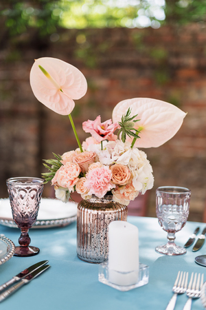 Flower table decorations for holidays and wedding dinner. Table set for holiday, event, party or wedding reception in outdoor restaurant. Stock Photo