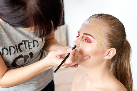 Professional makeup artist working with beautiful blonde young woman. Backstage scene: creative make-up master applies eye shadow. Beautiful woman face. Makeup detail. Beauty girl with perfect skin