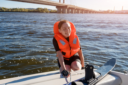 staying fit: Young fit woman ready to ride water skis siting on the boat closeup. Athlete water skiing and having fun. Living a healthy lifestyle and staying active. Water sports theme