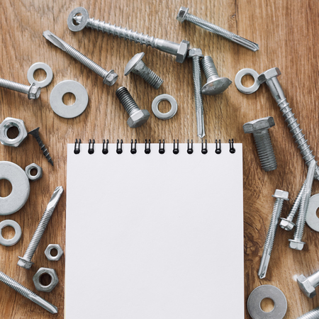 bolts and nuts: Construction tools. The screws, nuts and bolts arranged around blank spiral bound note book paper on wooden background. Repair, home improvement concept. Free space for text, top view, flat lay.