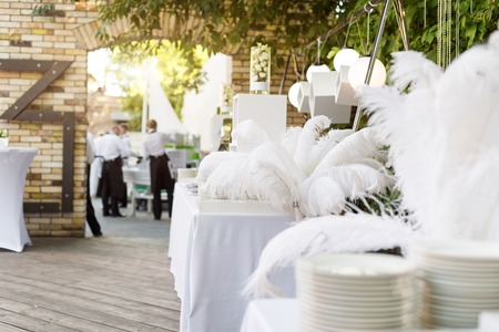 wedding reception decoration: Blurred background, professional waiters on duty. Outdoor party with finger food. Catering service.