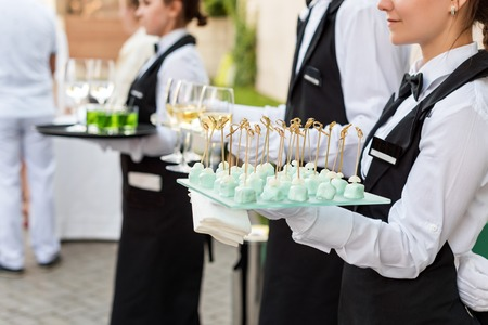 a meeting with a view to marriage: Midsection of professional waiters in uniform serving wine, cocktails and snacks during buffet catering party, festive event or wedding. Full glasses of champagne on tray.