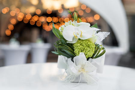 Flowers on the table in outdoor restaurant. Interior of a summer terrace of cafe. Table setting for wedding reception or an event. Copy space for text. Stock Photo
