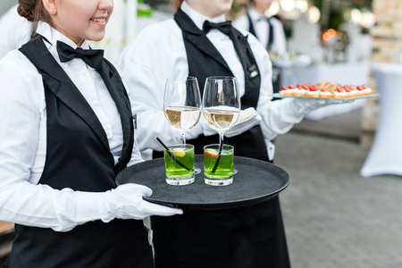 a meeting with a view to marriage: Midsection of professional waiters in uniform serving wine, cocktails and snacks during buffet catering party, festive event or wedding. Full glasses of wine on tray. Outdoor party catering service.