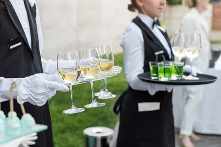 a meeting with a view to marriage: Midsection of professional waiters in uniform serving wine and snacks during buffet catering party, festive event or wedding. Full glasses of champagne on tray.