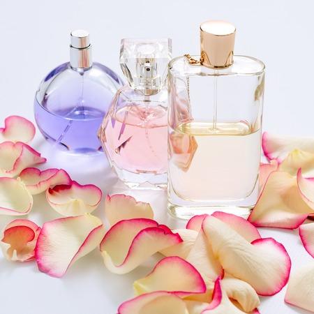 빛 배경에 꽃 꽃잎과 향수 병. 향수, 향수 컬렉션. 여성 액세서리. 스톡 콘텐츠