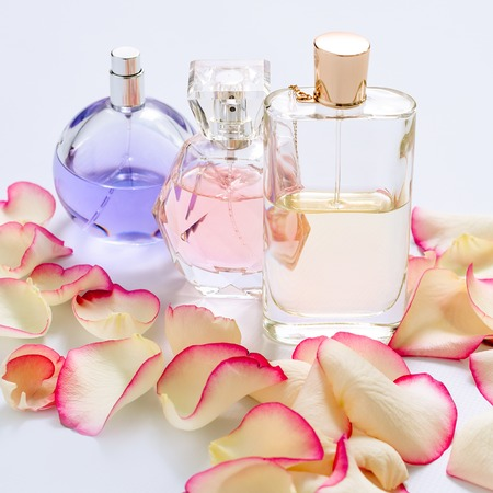 Perfume bottles with flower petals on light background. Perfumery, fragrance collection. Women accessories.
