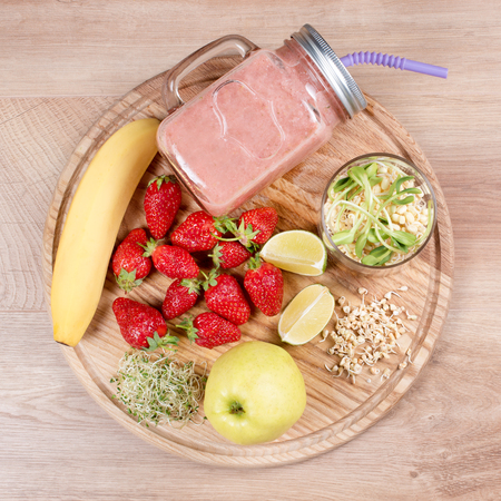 Detox cleanse drink, fruits and berries smoothie ingredients. Natural, organic healthy juice for weight loss diet or fasting day. Mason jar of dietary drink with strawberries, microgreens and banana