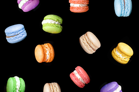 Multicolored macaroons isolated on black background falling or flying in motion. Traditional french dessert macarons Stock Photo