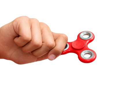 resting: Red hand spinner. Boy playing a popular toy fidget spinner in his hand. Stress relief. Anti stress and relaxation adhd attention fad boy concept.