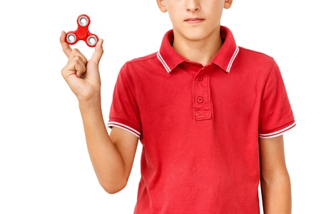 Red hand spinner. Boy playing a popular toy fidget spinner in his hand. Stress relief. Anti stress and relaxation adhd attention fad boy concept.