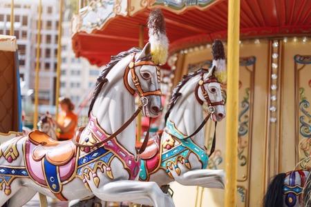 Paarden op een carnaval Merry Go Round. Oude Franse carrousel in een vakantiepark. Grote rotonde op markt in pretpark. Stockfoto