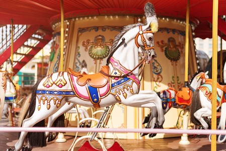 Horses on a carnival Merry Go Round. Old French carousel in a holiday park. Big roundabout at fair in amusement park. Stock Photo