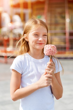 Cute little girl eating candy apple at fair in amusement park.