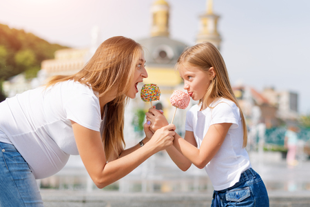 Cute little girl and her pregnant mother eating candy apples at fair in amusement park. Happy loving family. Mother and daughter having fun together.