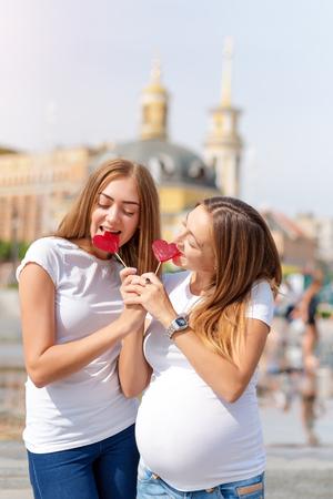 Lesbianas madres, pareja embarazada, feliz familia samesex en el parque de la ciudad en verano. Mujeres comiendo dulces, caramelos en forma de corazón, símbolo de amor.