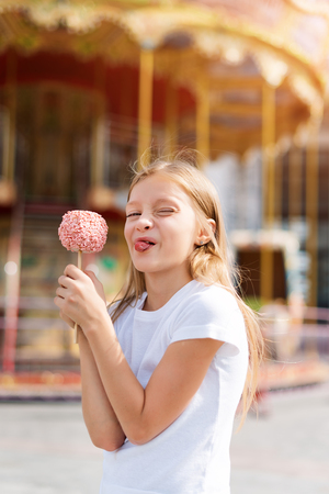 Cute little girl eating candy apple and posing at fair in amusement park.